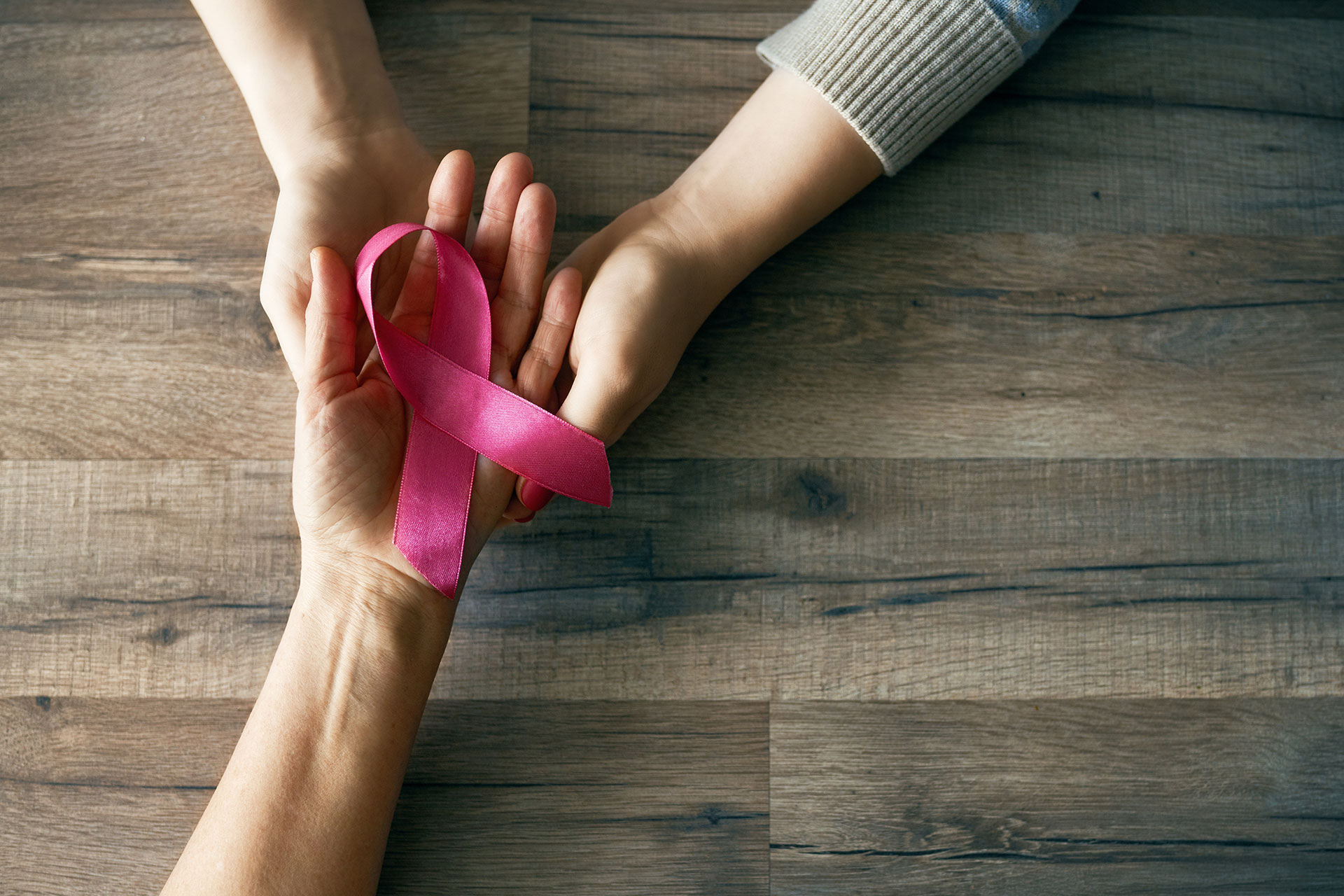 Two hands holding breast cancer awareness ribbon
